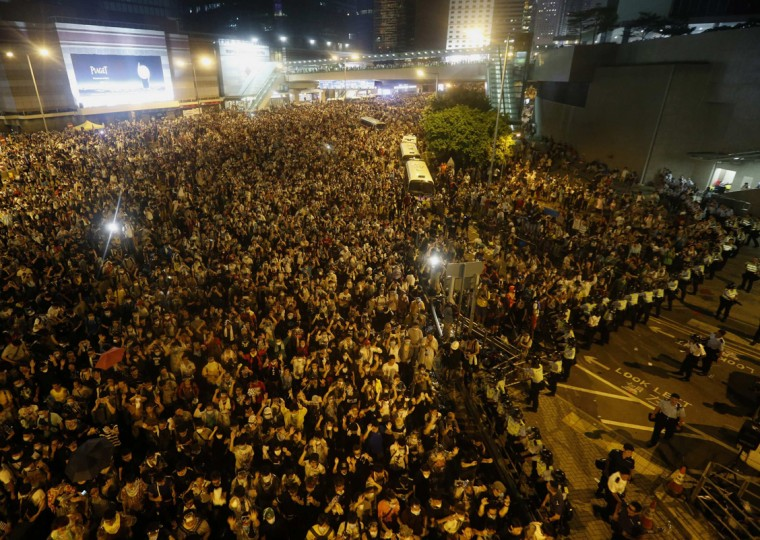 Riot police patrol as tens of thousands of protesters block the main street to the financial Central district (at background) outside the government headquarters in Hong Kong September 28, 2014. Riot police advanced on Hong Kong democracy protesters in the early hours of Monday, firing volleys of tear gas that sent some fleeing as others erected barricades to block the security forces in the heart of the former British colony. Earlier, police baton-charged a crowd blocking a key road in the government district in defiance of official warnings that the demonstrations were illegal. Picture taken September 28, 2014. (Bobby Yip/Reuters)