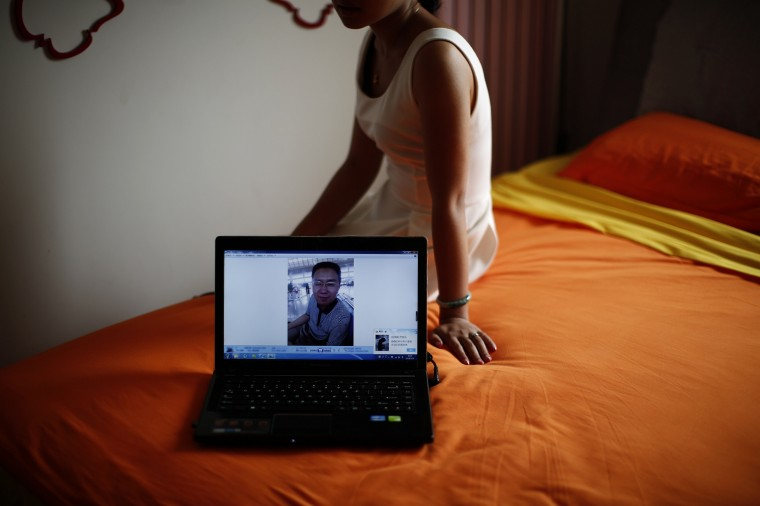 Liu, whose husband Lu was onboard Malaysia Airlines Flight MH370 which disappeared on March 8, 2014, shows her husband's picture on his laptop during an interview with Reuters in Beijing July 18, 2014, shows her husband's picture on his laptop as she sits on a bed they shared together at her home. They got married on March 1st, a week before the incident and could not go on a honeymoon due to her husband's busy schedule which was also the reason he had boarded the vanished plane. Six months after Malaysia Airlines Flight MH370, with 239 mostly Chinese people on board, disappeared about an hour into a routine journey from Kuala Lumpur to Beijing March 8, loved ones of missing passengers derive what comfort they can from what's left behind after the world's greatest aviation mystery. (Kim Kyung-Hoon/Reuters)