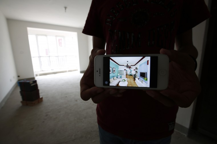 Zhiliang, whose fiancee was onboard Malaysia Airlines Flight MH370 which disappeared on March 8, 2014, shows an image on his mobile phone, which his fiancee chose for the reference to decorate their newly purchased house, during an interview with Reuters in Tianjin, August 26, 2014. Zhiliang said he will wait for his missing fiancee forever. They had planned to marry this year. (Kim Kyung-Hoon/Reuters)