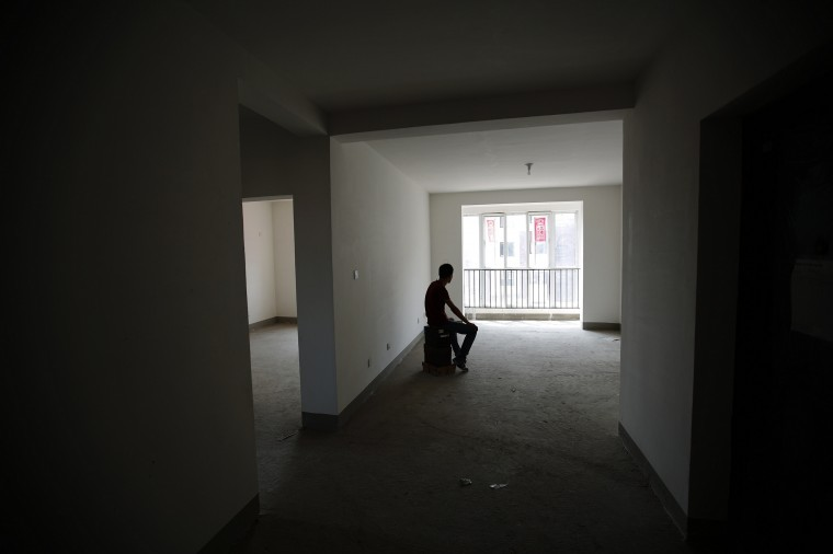 Zhiliang, whose fiancee was onboard Malaysia Airlines Flight MH370 which disappeared on March 8, 2014, is silhouetted at an empty house which he had planned to decorate with her for their marriage, after he showed the house during an interview with Reuters in Tianjin, August 26, 2014. Zhiliang said he will wait for his missing fiancee forever. They had planned to marry this year. Six months after Malaysia Airlines Flight MH370, with 239 mostly Chinese people on board, disappeared about an hour into a routine journey from Kuala Lumpur to Beijing March 8, loved ones of missing passengers derive what comfort they can from what's left behind after the world's greatest aviation mystery. (Kim Kyung-Hoon/Reuters)