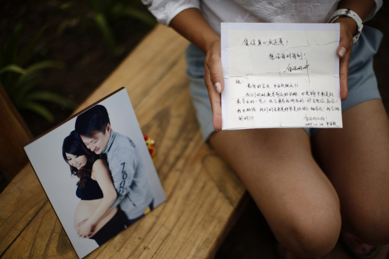 Cheng Liping, whose husband Ju was onboard Malaysia Airlines Flight MH370 which disappeared on March 8, 2014, shows a picture of she and her husband together and an old card with a message given by her husband, at a park near her house where she and her husband used to visit during an interview with Reuters in Beijing July 24, 2014. Cheng said her life has been totally changed since the incident. Their two little sons, who don't know about this incident, keep asking her when their dad is coming back. (Kim Kyung-Hoon/Reuters)