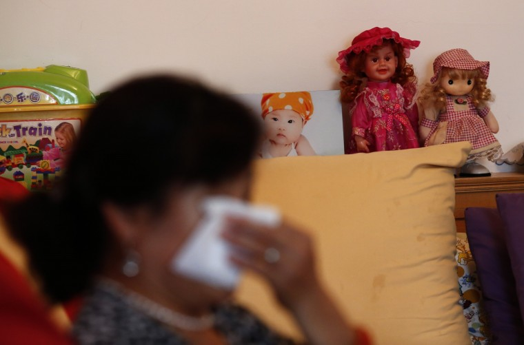 Hu, whose son Zhao's whole family was onboard Malaysia Airlines Flight MH370 which disappeared on March 8, 2014 wipes her tears during an interview with Reuters in Beijing July 24, 2014 as her granddaughter's framed picture is seen in the living room of her house. Hu said she had thought of committing suicide. She could not go back home for a while after the incident because she was afraid of entering the empty house which had been full of her 3 year-old granddaughter's lovely smile. Six months after Malaysia Airlines Flight MH370, with 239 mostly Chinese people on board, disappeared about an hour into a routine journey from Kuala Lumpur to Beijing March 8, loved ones of missing passengers derive what comfort they can from what's left behind after the world's greatest aviation mystery. More than two dozen countries have been involved in the air, sea and underwater search for the Boeing 777 but months of sorties failed to turn up any trace - even after narrowing the search area to the southern Indian Ocean - long after batteries on the black box voice and data recorders had gone flat. Picture taken July 24, 2014. (Kim Kyung-Hoon/Reuters)
