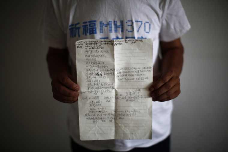 Zhang Yongli, whose daughter Zhang Qi was onboard Malaysia Airlines Flight MH370 which disappeared on March 8, 2014 shows a note featuring a poem which Zhang wrote for his daughter, during an interview with Reuters in Beijing July 22, 2014. Zhang said this incident is disrupting his and his wife's lives now. His wife sometimes roams several kilometres far from home because she cannot stand staying in their home from which her daughter is now absent. (Kim Kyung-Hoon/Reuters)