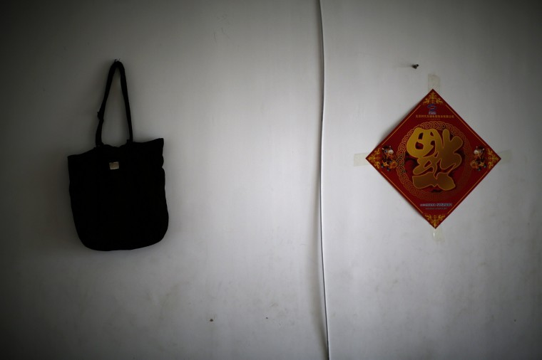 Dai Shuqin' bag (L), which was a gift from her missing younger sister a long time ago, is hung on a wall for a photograph during an interview with Reuters in Beijing July 22, 2014. Dai's sister's whole family was onboard Malaysia Airlines Flight MH370 which disappeared on March 8, 2014. Dai said she cannot go out without the bag these days because this bag makes her feel her sister is by her side when she carries the bag. (Kim Kyung-Hoon/Reuters)