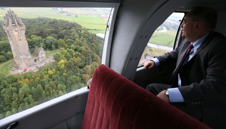 First Minister of Scotland Alex Salmond poses for a photograph as he flies past the Wallace Monument, Stirling, on September 16, 2014. (REUTERS/Paul Hackett)