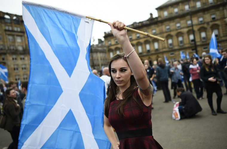 A woman waves a Scottish Saltire at a 'Yes' campaign rally in Glasgow, Scotland on September 17, 2014. (REUTERS/Dylan Martinez)