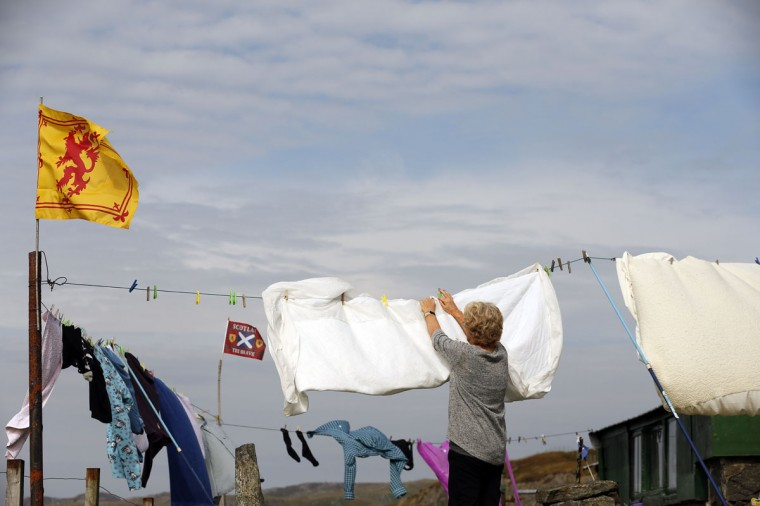 A woman hangs out her washing on the Isle of Lewis in the Outer Hebrides on September 11, 2014. (REUTERS/Cathal McNaughton)