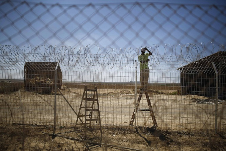 An Israeli worker repairs a fence damaged by a tank in Kibbutz Nahal Oz , just outside the northern Gaza Strip, September 3, 2014. Israelis living on the Gaza border have warily returned home after fleeing constant mortar and rocket fire during a seven-week war, feeling it is just a matter of time before their villages are targeted again. Picture taken September 3, 2014. (Amir Cohen /Reuters)