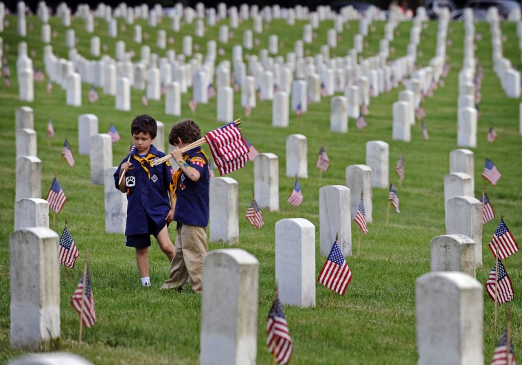 Michael Taylor, left, and Graham Houck, both 7 and of Ellicott City, take a rest after their Boy Scout Pack 323 helped place flags on veteran tombstones at the Baltimore National Cemetery. (Kenneth K. Lam/Baltimore Sun)