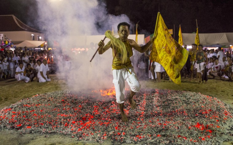 A devotee walks across hot coals outside Ban Tha Rue Shrine during fire walking ceremonies on September 29, 2014 in Phuket, Thailand. Ritual Vegetarianism in Phuket Island traces its roots back to the early 1800's. The annual festival begins on the first evening of the ninth lunar month and lasts for nine days. Participants in the festival perform acts of body piercing as a means of shifting evil spirits from individuals onto themselves and bring the community good luck. The ritualized mutilation is performed at a local Buddhist shrine under a trance-like state and is carefully supervised. (Damir Sagolj/Reuters)