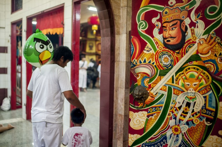 Vegetarian festival devotee with his kid and an angry bird baloon offer prayers at the Bang Neow shrine before a climbing on blades stairs performance on September 30, 2014 in Phuket, Thailand. (Borja Sanchez-Trillo/Getty Images)