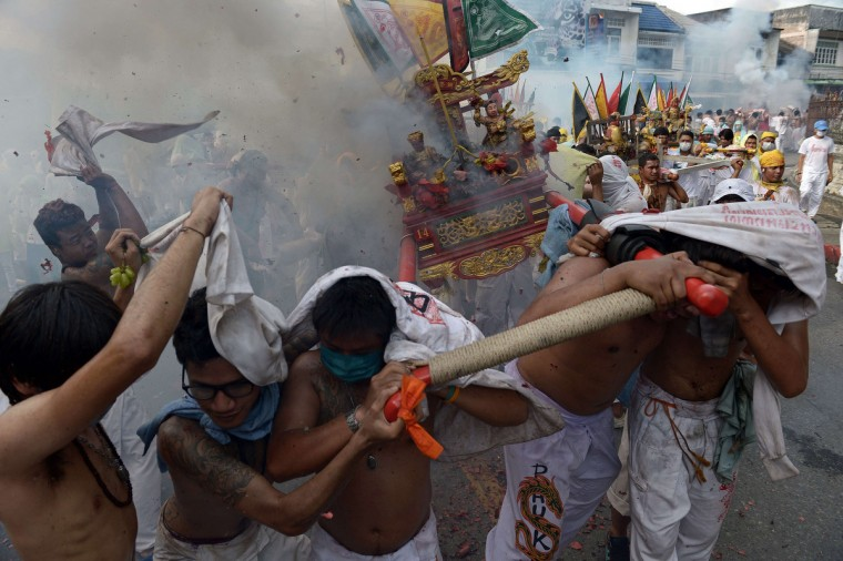 Devotees of the Chinese Bang Neow Shrine protect themselves as fire-crackers explode over idols they carry on a palanquin in a street procession during the annual Vegetarian Festival in the southern Thai town of Phuket on September 29, 2014. During the festival, which begins on the first evening of the ninth lunar month and lasts nine days, religious devotees slash themselves with swords, pierce their cheeks with sharp objects and commit other painful acts to purify themselves, taking on the sins of the community. (Christophe Archambault/Getty Images)