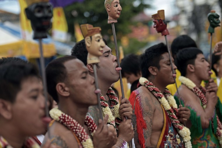 Devotees of the Chinese Bang Neow Shrine with metal rods inserted into their tongues take part in a street procession during the annual Vegetarian Festival in the southern Thai town of Phuket on September 29, 2014. (Christophe Archambault/Getty Images)