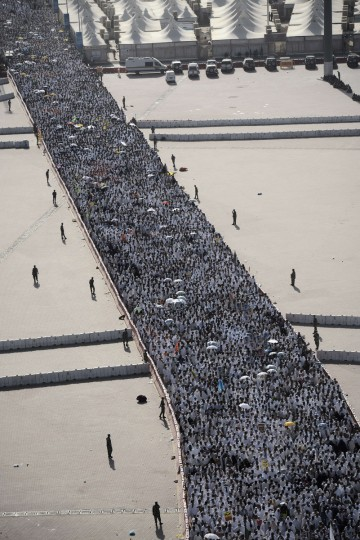 "Muslim pilgrims arrive to throw pebbles at pillars during the ""Jamarat"" ritual, the stoning of Satan, in Mina near the holy city of Mecca, on October 4, 2014. Pilgrims pelt pillars symbolizing the devil with pebbles to show their defiance on the third day of the hajj as Muslims worldwide mark the Eid al-Adha or the Feast of the Sacrifice, marking the end of the hajj pilgrimage to Mecca and commemorating Abraham's willingness to sacrifice his son Ismail on God's command in the holy city of Mecca. (Mohammed Al-Shaikh/Getty Images)"