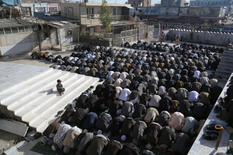 """Afghan men offer Eid al-Adha prayers as a child looks on in Ghazni province on October 4, 2014. Afghans started celebrating Eid al-Adha or """"Feast of the Sacrifice"""", which marks the end of the annual hajj or pilgrimage to Mecca and is celebrated in remembrance of Abraham's readiness to sacrifice his son to God. (Rahmatullah Alizadah/Getty Images)"""