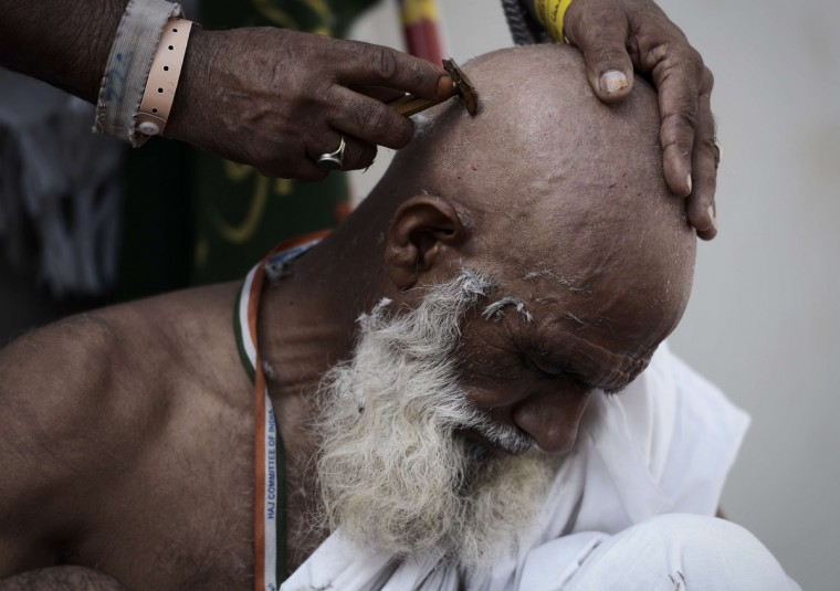 "Muslim pilgrims shave their hair after throwing pebbles at pillars during the ""Jamarat"" ritual, the stoning of Satan, in Mina near the holy city of Mecca, on October 4, 2014. Pilgrims pelt pillars symbolizing the devil with pebbles to show their defiance on the third day of the hajj as Muslims worldwide mark the Eid al-Adha or the Feast of the Sacrifice, marking the end of the hajj pilgrimage to Mecca and commemorating Abraham's willingness to sacrifice his son Ismail on God's command in the holy city of Mecca. (Mohammed Al-Shaikh/Getty Images)"