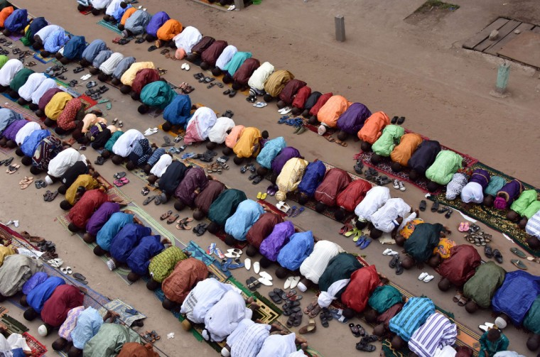 "People pray during the Muslim festival of Eid al-Adha, on October 4, 2014 in Marcory, a neighborhood of Abidjan. Eid al-Adha, celebrated by Muslims around the world, coincides with the symbolic stoning of the devil by pilgrims gathered for the annual hajj near the holy city of Mecca in western Saudi Arabia. Eid al-Adha is known as ""Tabaski"" in western Africa. (Sia Kambou/Getty Images)"
