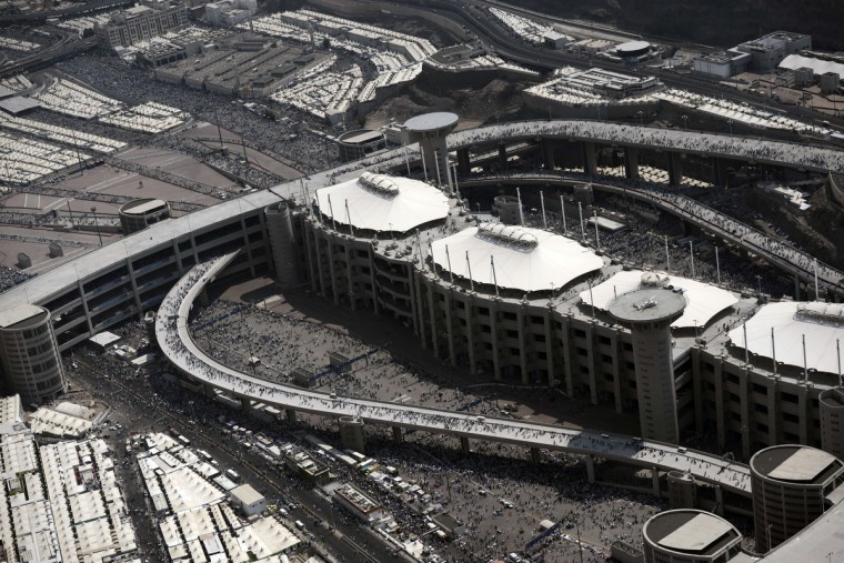 """An aerial view of the walk way leading to the pillars where pilgrims throw stone (center tents) on the 2nd day of """"Jamarat"""" ritual, the stoning of Satan, in Mina near the holy city of Mecca, on October 5, 2014. Pilgrims pelt pillars symbolising the devil with pebbles to show their defiance on the third day of the hajj as Muslims worldwide mark the Eid al-Adha or the Feast of the Sacrifice, marking the end of the hajj pilgrimage to Mecca and commemorating Abraham's willingness to sacrifice his son Ismail on God's command in the holy City of Mecca. (Mohammed Al-Shaikh/Getty Images)"""