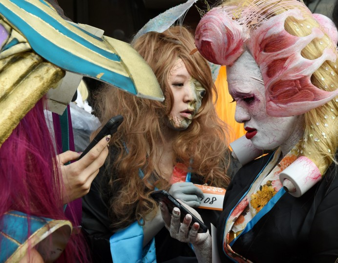 Participants dressed in costumes use their phones as they wait for the Halloween Parade in Kawasaki, a suburb of Tokyo, on October 26, 2014. More than 100,000 visitors watched the street costume parade in which some 2,500 people took part. (Toru Yamanaka/Getty Images)