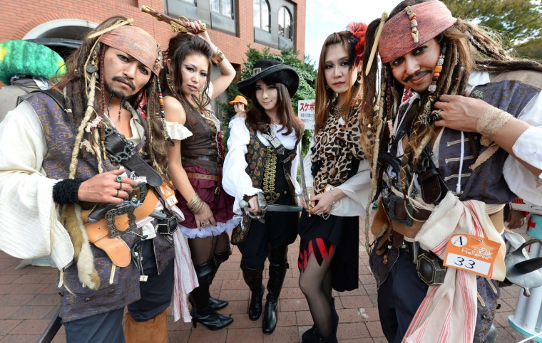 Participants wear costumes as they pose for pictures before the Halloween Parade in Kawasaki, a suburb of Tokyo, on October 26, 2014. More than 100,000 visitors watched the street costume parade in which some 2,500 people took part. (Toru Yamanaka/Getty Images)