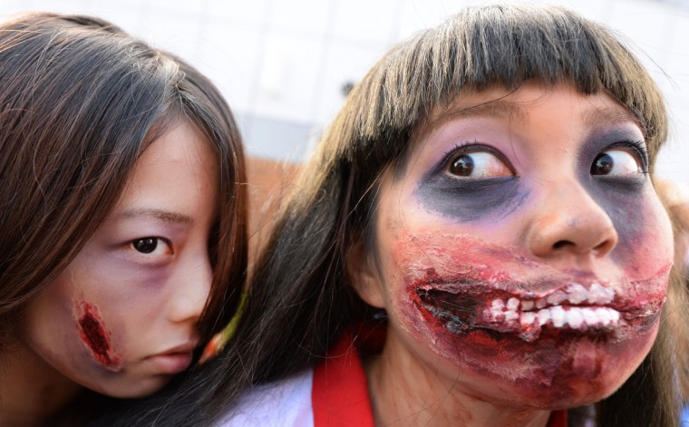 Participants make up as they pose for pictures before the Halloween Parade in Kawasaki, a suburb of Tokyo, on October 26, 2014. More than 100,000 visitors watched the street costume parade in which some 2,500 people took part. (Toru Yamanaka/Getty Images)