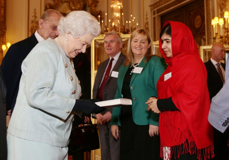 Malala Yousafzai presents a copy of her book to Queen Elizabeth II and Prince Philip, Duke of Edinburgh during a Reception for Youth, Education and the Commonwealth at Buckingham Palace on October 18, 2013 in London, England. (Yui Mok/WPA Pool/Getty Images)