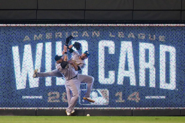 Jonny Gomes #15 and Sam Fuld #23 of the Oakland Athletics collide on a triple hit by Eric Hosmer #35 of the Kansas City Royals in the 12th inning during the American League Wild Card game at Kauffman Stadium in Kansas City, Missouri. (Ed Zurga/Getty Images)