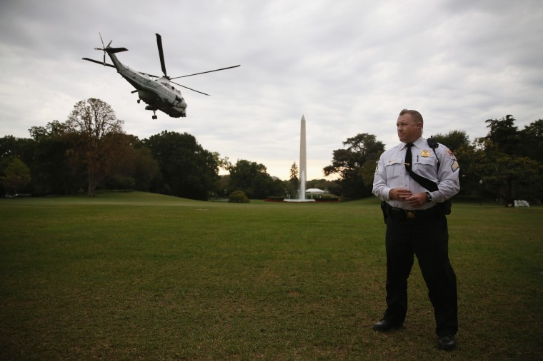 A member of the U.S. Secret Service stands guard as Marine One carrying U.S. President Barack Obama takes off from the South Lawn of the White House October 7, 2014 in Washington, DC. Obama is traveling to New York to attend high ticket fundraisers for the Democratic Party. (Mark Wilson/Getty Images)