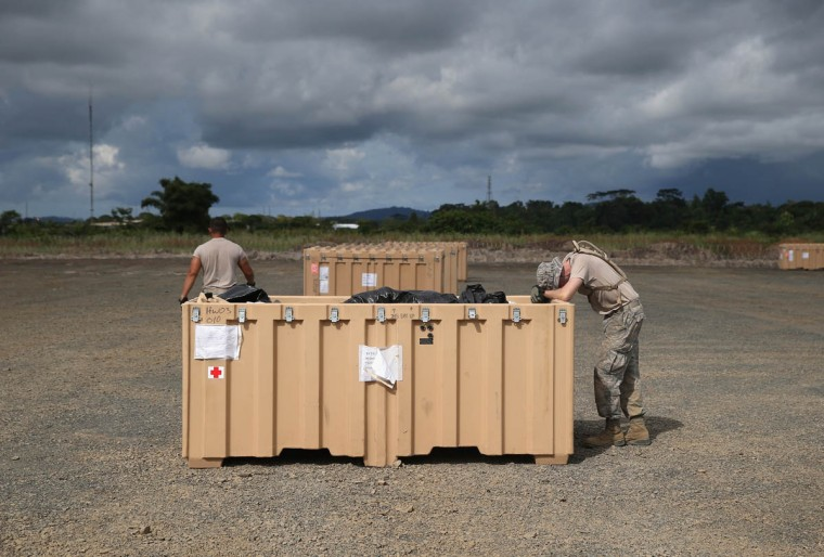 Exhausted from the tropical heat, a U.S. Air Force airmen rests after a day of setting up a 25-bed hospital to aid Liberian health workers infected with Ebola on October 8, 2014 near Monrovia, Liberia. The airmen are constructing the modular hospital, known by the military as an expeditionary medical support system (EMEDS), near the international airport outside of Monrovia. The airmen will train U.S. public health service members in using the hospital's medical equipment, but will not be involved in treatment of Ebola patients. (John Moore/Getty Images)