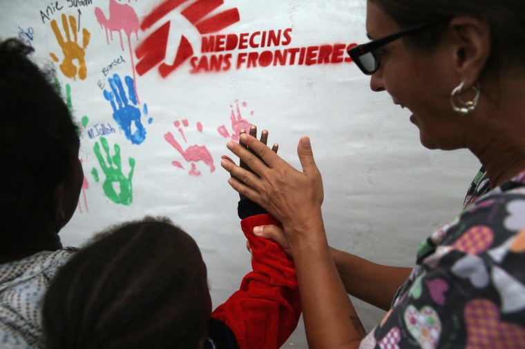 A mother and child put their handprints on a piece of artwork made by outgoing Ebola survivors from the Doctors Without Borders (MSF), treatment center on October 12, 2014 in Paynesville, Liberia. Roughly 40 percent of people who come down with Ebola survive. According to the World Health Organization, the Ebola epidemic has killed more than 4,000 people in West Africa. (Photo by John Moore/Getty Images)