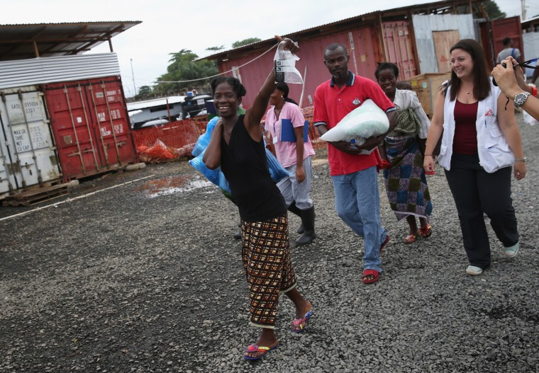 Ebola survivor Sontay Massaley, 37, smiles with Doctors Without Borders (MSF), staff after being released from the MSF treatment center on October 12, 2014 in Paynesville, Liberia. In her hand she held a bag containing her cell phone, which had been disinfected. She said she was there for eight days, after having first arrived sick and tested positive for the disease. Massaley has three children, all healthy, and works as a vendor an an outdoor market. She did not know from whom she contracted Ebola. (Photo by John Moore/Getty Images)