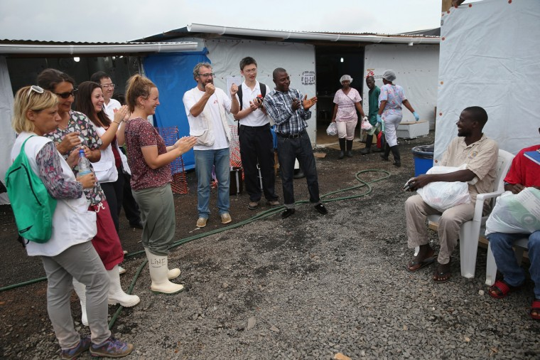 Doctors Without Borders (MSF), staff cheer as Ebola survivors are out-processed from the treatment center after recovering from the virus on October 12, 2014 in Paynesville, Liberia. About 40 percent of people who contract the disease survive. According to the World Health Organization, the Ebola epidemic has killed more than 4,000 people in West Africa. (Photo by John Moore/Getty Images)