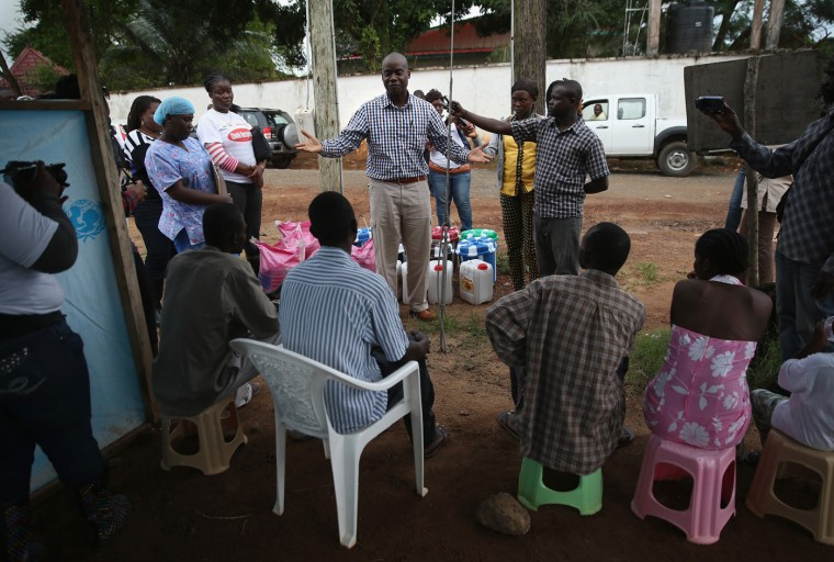 Emergency room doctor and Ebola survivor Philip Ireland congratulates fellow survivors after they were released from the JFK Ebola treatment center on October 13, 2014 in Monrovia, Liberia. A planned strike at Ebola treatment centers was averted as most nurses and health care workers reported for work, many saying they could not in good conscience leave their patients unattended. Health workers have been asking for increased hazard pay. They are one of the most high-risk groups of Ebola infection, and nearly 100 of them have died in Liberia alone. (Photo by John Moore/Getty Images)
