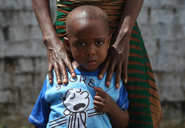Ebola survivor James Mulbah, 2, stands with his mother, Tamah Mulbah, 28, who also recovered from Ebola in the low-risk section of the Doctors Without Borders (MSF), Ebola treatment center after survivors' meeting on October 16, 2014 in Paynesville, Liberia. The virus has a 70 percent mortality rate, according to the World Health Organization, but leaves survivors immune to the strain that sickened them. (Photo by John Moore/Getty Images)