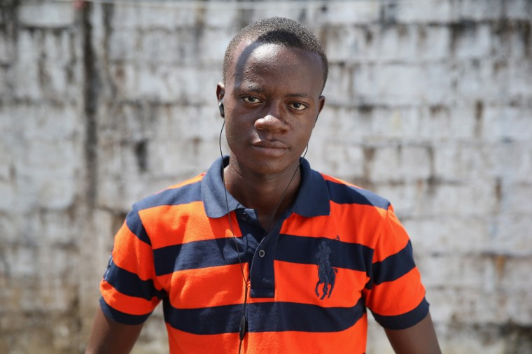 Ebola survivor Eric Forkpa, 23, stands in the low-risk section of the Doctors Without Borders (MSF), Ebola treatment center after meeting with fellow survivors on October 16, 2014 in Paynesville, Liberia. The college student, majoring in civil engineering, said he thinks he caught Ebola while caring for his sick uncle, who died of the disease. He spent 18 days at the MSF center recovering from the virus. The virus has a 70 percent mortality rate, according to the World Health Organization, but leaves survivors immune to the strain that sickened them. (Photo by John Moore/Getty Images)