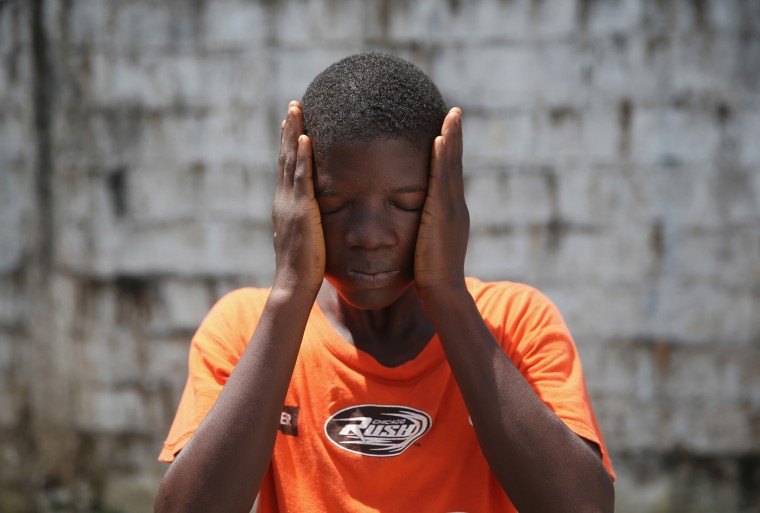 Ebola survivor Jeremra Cooper, 16, wipes his face from the heat while in the low-risk section of the Doctors Without Borders (MSF), Ebola treatment center on October 16, 2014 in Paynesville, Liberia. The 8th grade student said he lost six family members to the Ebola epidemic before coming down sick with the disease himself and being sent to the MSF center, where he recovered after one month. The virus has a 70 percent mortality rate, according to the World Health Organization, but leaves survivors immune to the strain that sickened them. (Photo by John Moore/Getty Images)
