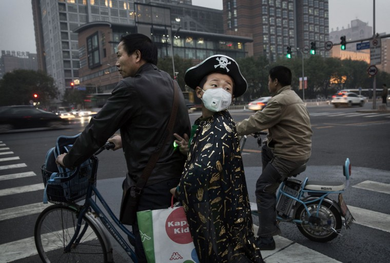 A Chinese boy dressed as a pirate for Halloween wears a facemask due to pollution on a hazy day on October 31, 2014 in Beijing, China. (Kevin Frayer/Getty Images)