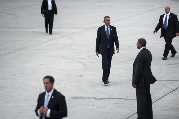 Members of the US Secret Service escort US President Barack Obama as he walks to Air Force One at Gary Chicago International Airport on October 2, 2014 in Gary, Indiana. Obama is returning to Washington after a trip to Illinois where he attended a fundraiser and spoke about the economy. (Brendan Smialowski/AFP/Getty Images)