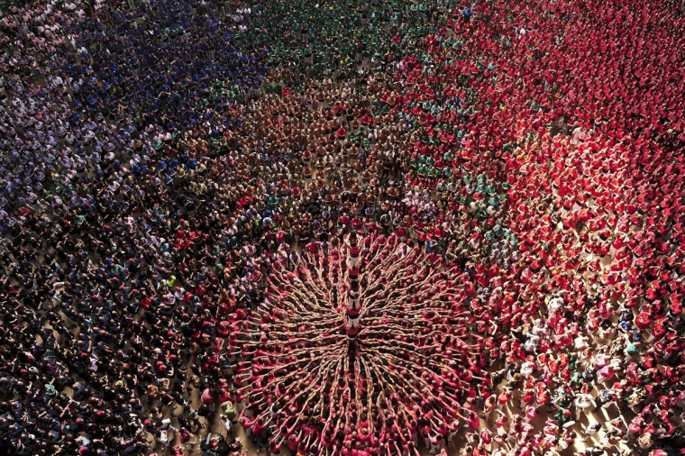 "Members of the ""Colla Vella Xiquets de Valls"" human tower team form a ""castell"" during the XXV human towers, or castells, competition in Tarragona on October 35, 2014. These human towers, built traditionally in festivals within Catalonia, gather several teams that attempt to build and dismantle a tower structure. (Josep Lago /AFP/Getty Images)"
