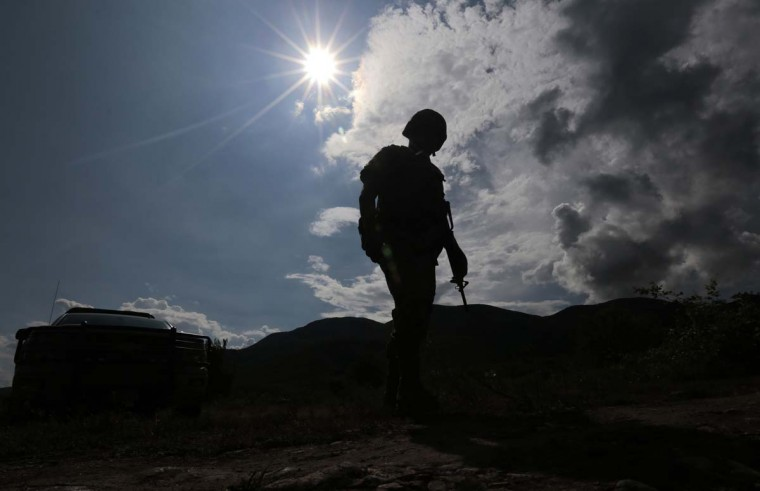 A Mexican marine stands guard at Pueblo Viejo, in the outskirts of Iguala, Guerrero state, Mexico, where a mass grave was found on October 5, 2014. At least 21 bodies were pulled from a mass grave in southern Mexico and authorities checked Sunday if they were among a group of 43 students missing since a police shooting last week. (Pedro Pardo/AFP/Getty Images)