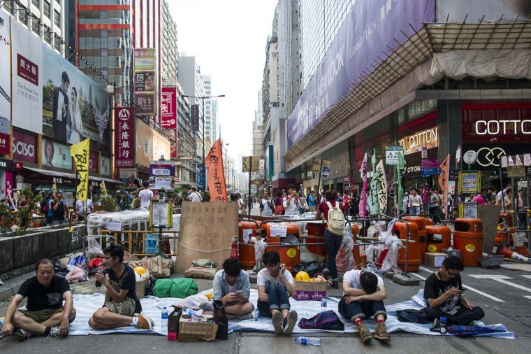 Pro-democracy protesters sit in front of a barricade in the Mongkok district of Hong Kong on October 6, 2014. Exhausted Hong Kong demonstrators debated the next step in their pro-democracy campaign on October 6 as their numbers dwindled after a week of rallies, and the city returned to work despite road closures and traffic gridlock. (Xaume Olleros/AFP/Getty Images)