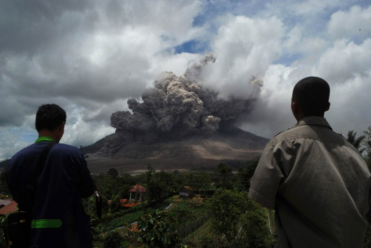 Residents watch as dark giant ash clouds rise from the crater of Mount Sinabung volcano during an eruption on October 8, 2014, as seen from Karo district located on Indonesia's Sumatra island, following an earlier eruption on October 5, 2014. According to authorities hundreds of residents are still housed at evacuation centers as authorities maintain off limit danger zone around Mount Sinabung located in Indonesia's Sumatra island following deadly eruption in early February that killed about 17 people. (Sutanta Aditya/Getty Images)
