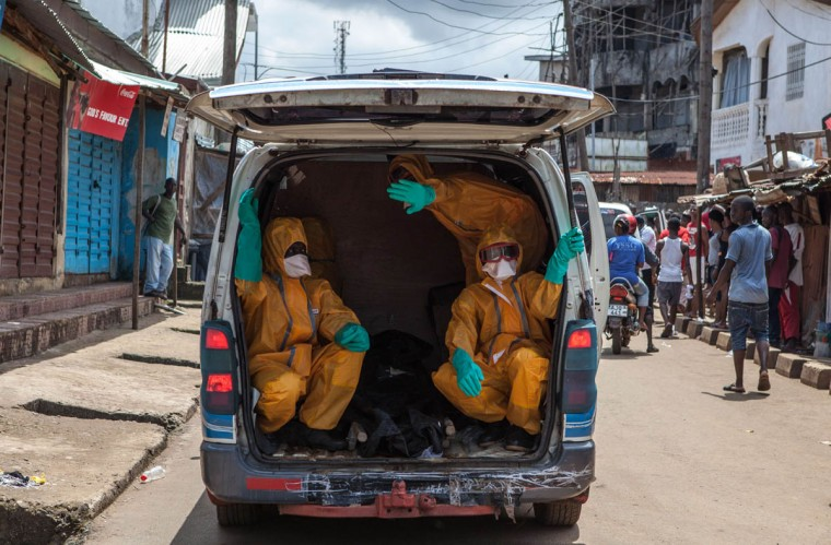 Volunteers arrive to pick up bodies of people who died of the Ebola virus, against a 100 US dollar weekly risk-taking compensation, on October 8, 2014 in Freetown. Dozens of British military personnel are due to fly to Sierra Leone next week to help build medical facilities to combat the Ebola epidemic, the defence ministry said on October 7. (Florian Plaucheur/Getty Images)
