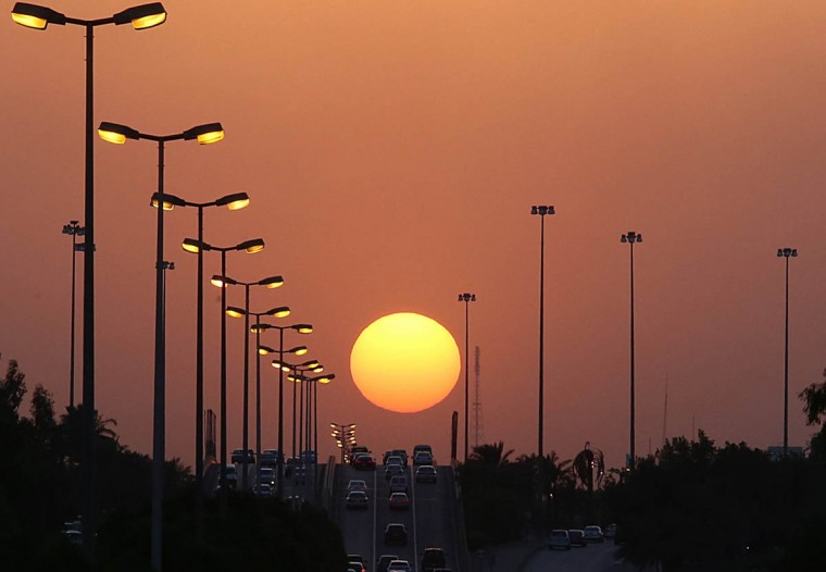 The sun sets over a main highway in Kuwait City on October 8, 2014. Temperature in Kuwait dropped below 40 degrees Celsius this week after reaching a high of 50 degrees Celsius during the summer. (Yasser Al-Zayvat/Getty Images)