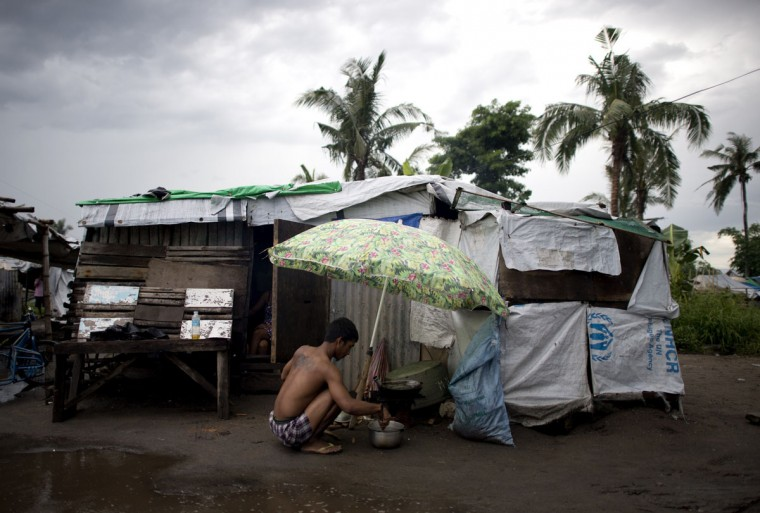 A man cooks dinner in front of his makeshift house at a tent city in Tacloban on the eastern island of Leyte on October 14, 2014. The town was devastated by typhoon Haiyan in 2013. The storm, the strongest ever to hit land, left more than 7,000 dead or missing and ravaged whole cities when it struck on November 8, 2013. (NOEL CELIS/AFP/Getty Images)
