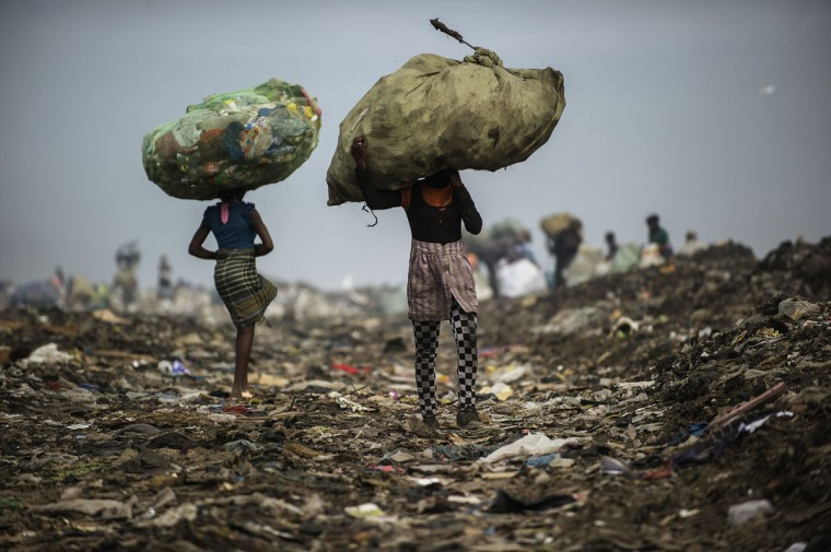 Girls carry bags of plastic items and tins as rubbish pickers sift through garbage at the Maputo municipal garbage dumping site in Maputo on October 14, 2014. (GIANLUIGI GUERCIA/AFP/Getty Images)