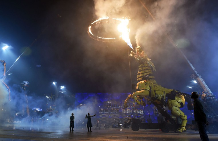 "A French-made ""Long Ma,"" a mechanical dragon horse, spews fire during a performance between the Bird's Nest National Stadium and Water Cube (at rear) in Beijing on October 19, 2014. (GREG BAKER/AFP/Getty Images)"
