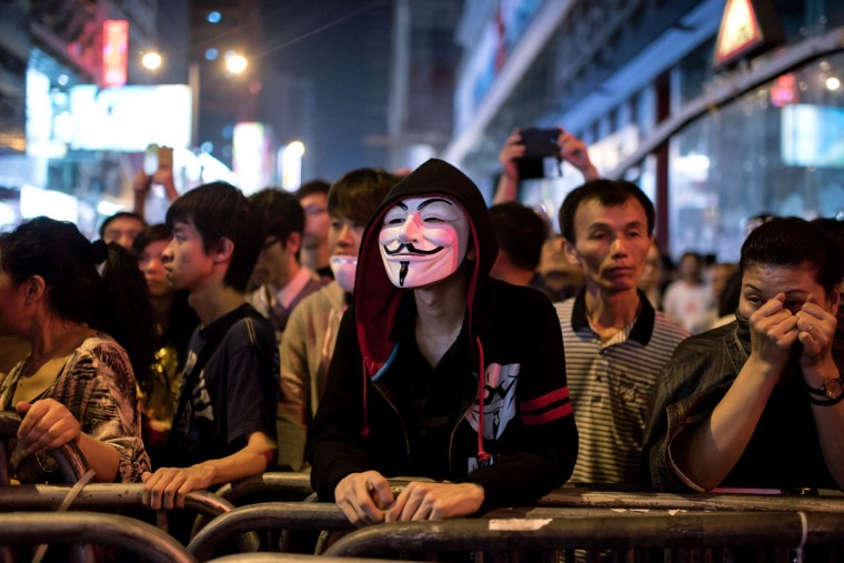 A pro-democracy protester wearing a Guy Fawkes mask stands at a barricade during a stand-off with police in the Mongkok district of Hong Kong on October 19, 2014. (Alex Ogle/AFP/Getty Images)