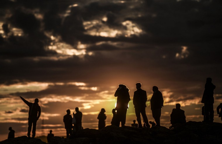 Kurdish people watch the Syrian town of Kobane, also known as Ain al-Arab, at sunset from the southeastern village of Mursitpinar, Sanliurfa province, on October 19, 2014. (BULENT KILIC/AFP/Getty Images)