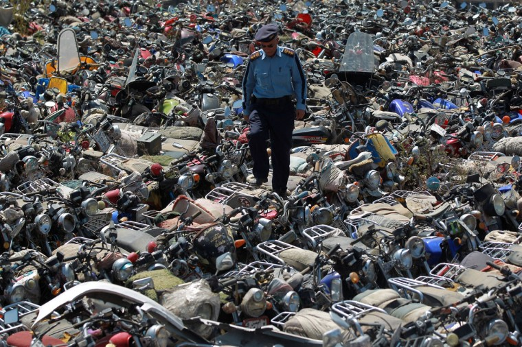 A Yemeni policeman walks on motorcycles that were seized after their owners violated a ban on motorcycles on October 20, 2014, at the police headquarters in the capital Sanaa. (MOHAMMED HUWAIS/AFP/Getty Images)